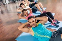 Homem novo considerável que sorri ao exercitar a trituração lateral no gym foto de stock royalty free