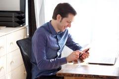 Homem novo considerável que sorri e que guarda o telefone celular imagem de stock royalty free