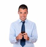 Homem novo considerável que texting com seu telefone celular foto de stock