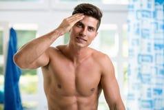 Homem novo considerável que toca em seu cabelo imagens de stock royalty free