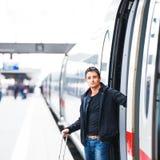 Homem novo considerável que toma um trem Foto de Stock Royalty Free