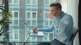 Homem novo considerável que trabalha com portátil, dentro video estoque