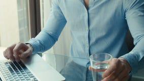 Homem novo considerável que trabalha com portátil, dentro vídeos de arquivo