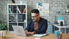 Homem novo considerável que usa o Internet para encontrar a informação então escrever no caderno vídeos de arquivo