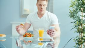Homem novo considerável que usa o telefone durante o café da manhã filme