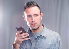 Homem novo considerável que usa seu telefone esperto no por do sol/alvorecer no cit foto de stock royalty free