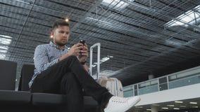 Homem novo considerável que usa Smartphone e trabalhando no aeroporto ao esperar o seu fila pelo registro, viajando Fotos de Stock Royalty Free