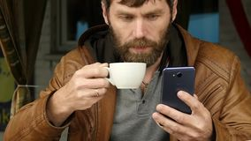 Homem novo considerável que usa um smartphone, sentando-se em um café e em um café exteriores das bebidas Movimento lento video estoque