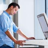 Homem novo considerável que usa uma máquina da cópia foto de stock