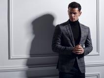Homem novo considerável, sério que levanta no estúdio perto da parede branca no terno elegantemente cinzento, sombra Conceito do  foto de stock