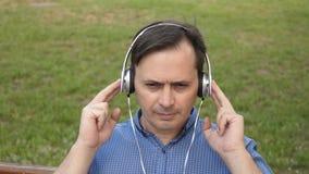 Homem novo consider?vel que escuta a m?sica de seu smartphone com os fones de ouvido, dan?ando fora no parque em um banco no vídeos de arquivo