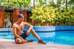 Homem novo consider?vel que inclina-se na borda da piscina e que sorri na c?mera em um clima tropical fotografia de stock royalty free