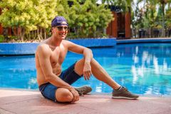 Homem novo consider?vel que inclina-se na borda da piscina e que sorri na c?mera em um clima tropical fotos de stock royalty free