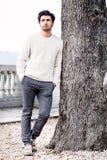Homem novo considerável apenas na natureza perto de uma árvore fora Imagem de Stock