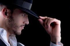 Homem novo considerável com um fundo do preto do chapéu Imagem de Stock