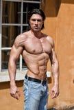 Homem novo considerável descamisado com as calças de brim vestindo do corpo muscular Foto de Stock