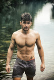 Homem novo considerável do músculo que está na lagoa de água, despida Imagem de Stock