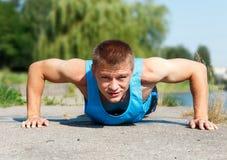 Homem novo considerável na boa forma que faz a flexão de braço quando tra exterior Imagem de Stock Royalty Free