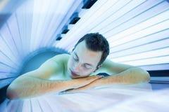 Homem novo considerável que relaxa durante uma sessão bronzeando-se Fotos de Stock Royalty Free