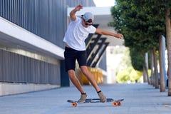 Homem novo considerável que skateboarding na rua Imagem de Stock