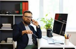Homem novo considerável que trabalha do escritório domiciliário e que usa o smartphone Fotos de Stock Royalty Free