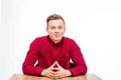 Homem novo considerável satisfeito no assento e no sorriso vermelhos da camisa Imagens de Stock Royalty Free