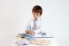 Homem novo, contando o dinheiro e tomando notas Fotos de Stock
