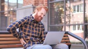 Homem novo da barba do ruivo com a dor nas costas que trabalha no portátil exterior video estoque