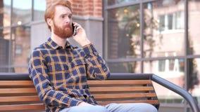 Homem novo da barba do ruivo que fala no telefone ao sentar-se exterior no banco filme