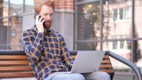 Homem novo da barba do ruivo que fala no telefone, sentando-se no banco vídeos de arquivo