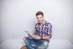 Homem novo da forma que guarda um computador da almofada da tabuleta Fotografia de Stock