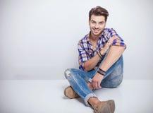 Homem novo da forma que senta-se no fundo branco do estúdio Fotos de Stock
