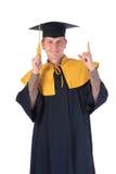 Homem novo da graduação que aponta o dedo para cima Foto de Stock Royalty Free