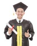 Homem novo da graduação que sorri ao guardar o diploma e ao dar o th Fotos de Stock