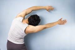 Homem novo da raça misturada no estiramento do lado da ioga Fotografia de Stock