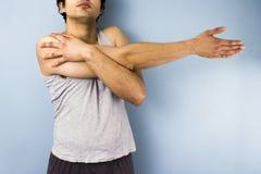 Homem novo da raça misturada que estica seu braço Fotografia de Stock