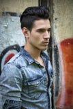 Homem novo de cabelo preto considerável na camisa da sarja de Nimes Foto de Stock