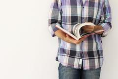 Homem novo de encontro à parede que lê um livro Fotos de Stock