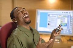 Homem novo de riso com telefone e computador de pilha Fotografia de Stock