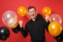 Homem novo de riso na camisa clássica preta que faz o gesto do vencedor em balões de ar vermelhos brilhantes do fundo ` S do Vale imagem de stock