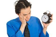 Homem novo de sono que guarda o despertador Foto de Stock