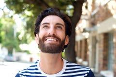Homem novo de sorriso com a barba que olha acima Imagens de Stock Royalty Free