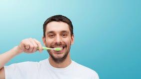 Homem novo de sorriso com escova de dentes imagem de stock royalty free