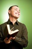 Homem novo de sorriso com livro fotografia de stock royalty free