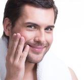 Homem novo de sorriso com mão perto da cara. Imagens de Stock