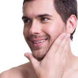 Homem novo de sorriso com mão perto da cara Imagens de Stock