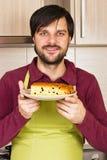 Homem novo de sorriso com o avental que guarda uma placa com bolo caseiro Imagem de Stock