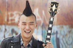Homem novo de sorriso com o Mohawk punk que guardara a guitarra fotos de stock royalty free