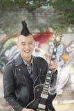 Homem novo de sorriso com o Mohawk punk que guardara a guitarra fotos de stock