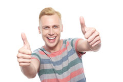 Homem novo de sorriso com polegares-acima Imagens de Stock